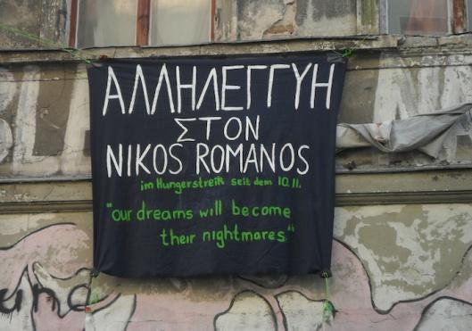 """""""Solidariedade com Nikos Romanos, em greve de fome desde 10 de Novembro. Os nossos sonhos tornar-se-ão os seus pesadelos"""""""