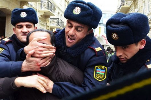 Three policemen man-handle one political activist during a protest in Baku, Azerbaijan, 12 March 2011.